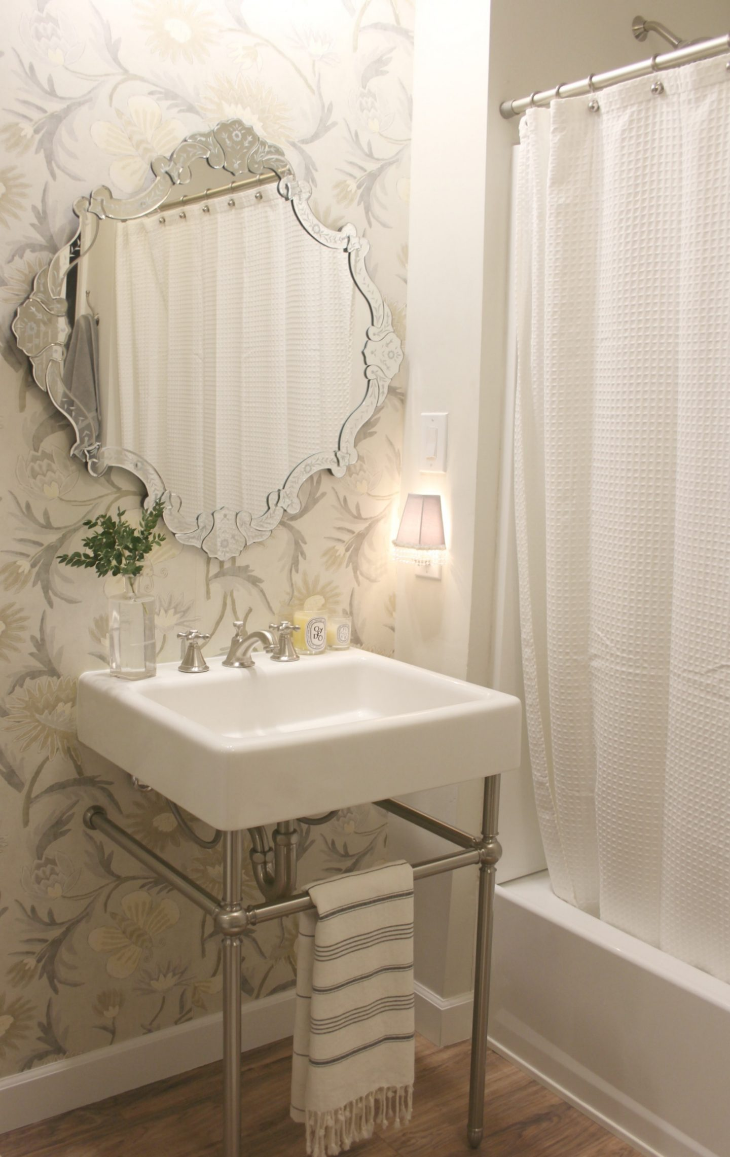 Classic bathroom with modern farmhouse fireclay console sink by DXV. Wallpaper is Thibaut. Venetian mirror. Come explore How to Decorate a Room Without Breaking the Bank: Low Cost Design Reminders.