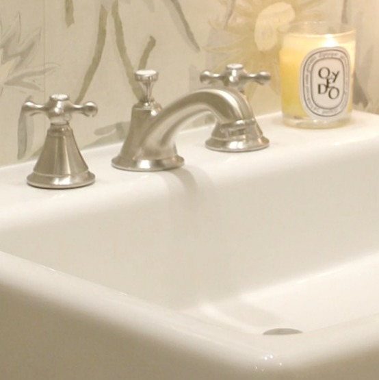 Detail of a gorgeous brushed nickel widespread Seabury bathroom faucet by #Grohe. The cross handles lend a nostalgic and classic feel. A Dyptique candle glows on the farm sink. #classicdecor #bathroomfaucet #bathroomsink