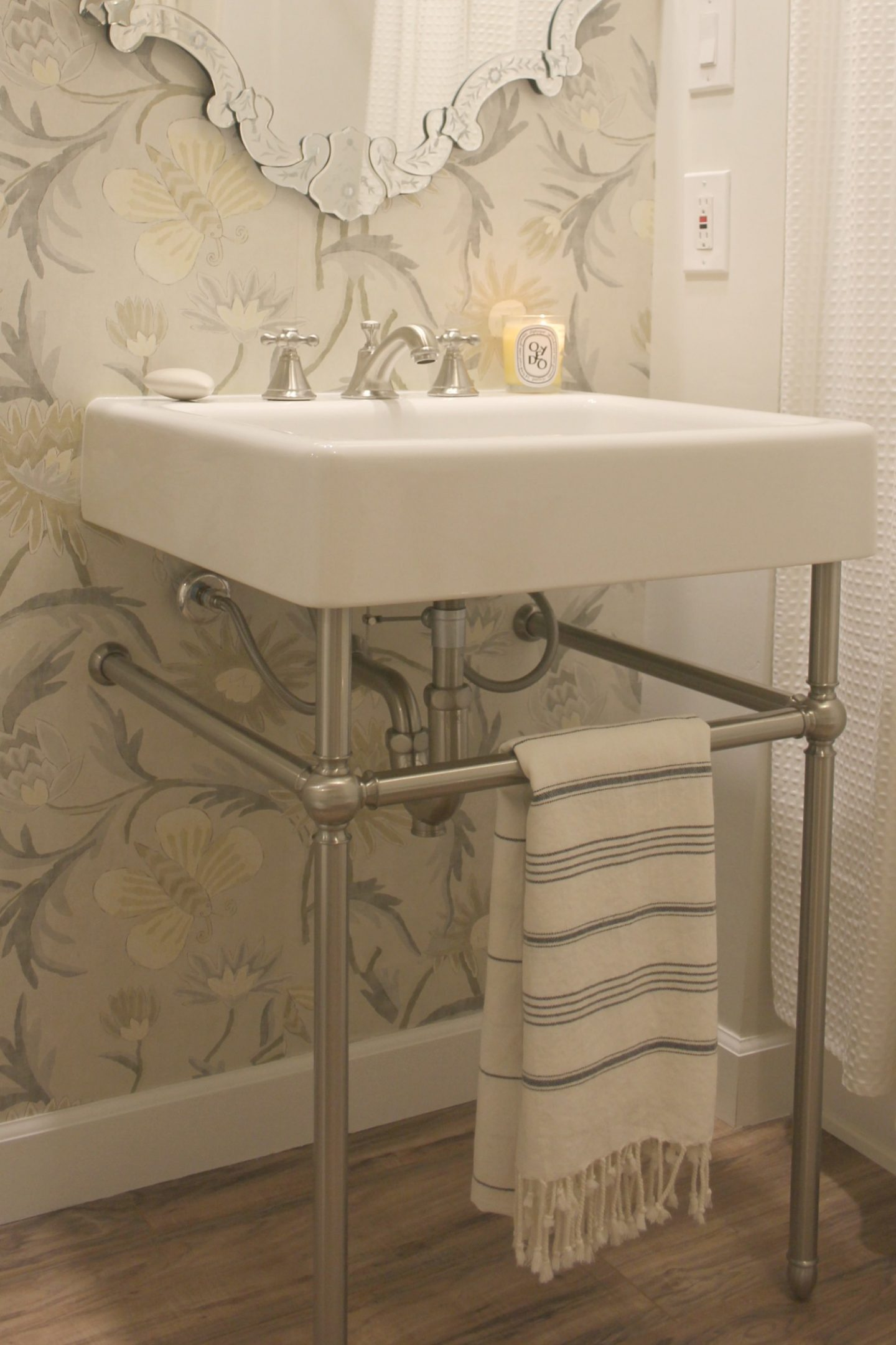 An elegant console sink, wallpaper, and a Venetian mirror in a classic, spa-like bathroom by Hello Lovely. #beforeandafter #bathroommakeover #DIY #renovation