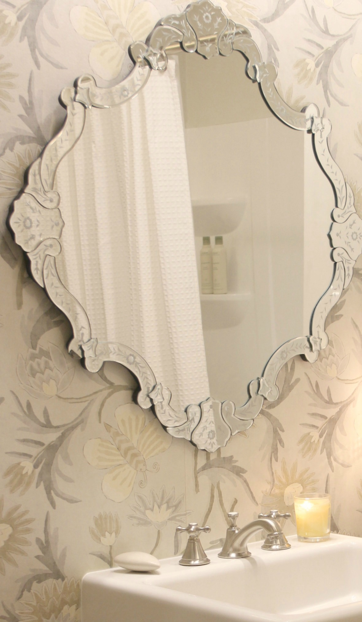 In a classic bathroom, fireclay modern farmhouse console sink. Venetian mirror over sink. Wallpaper is Thibaut. Come explore How to Decorate a Room Without Breaking the Bank: Low Cost Design Reminders.