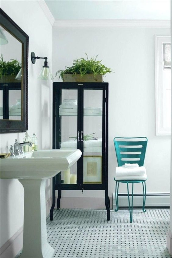 Glass Slipper by Benjamin Moore is the paint color on the walls and ceiling of this classic bathroom with pedestal sink and tall glass front cabinet. #benjaminmooreglassslipper #glassslipper #paintcolors #bathroomdesign
