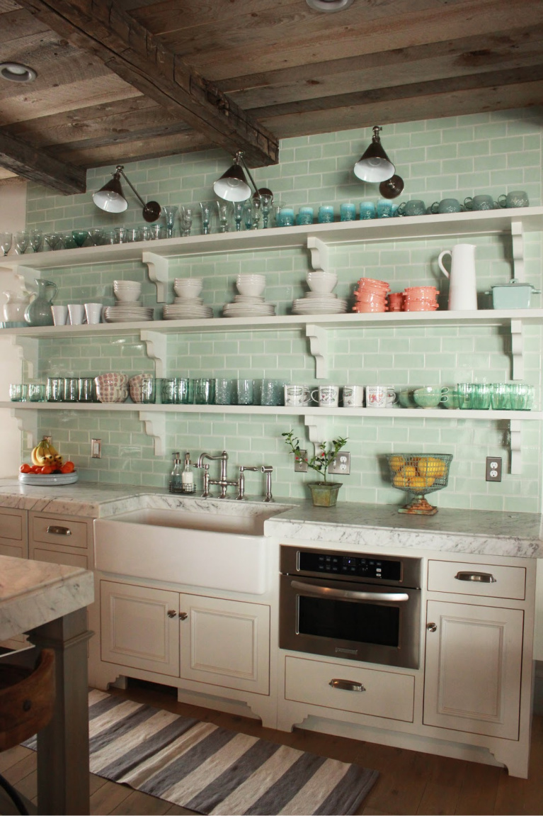 Open shelving and soft green subway tile backsplash in kitchen of Country French Old World style in a newly built custom cottage home in Utah - Decor de Provence. #countryfrench #interiordesign #oldworldstyle #europeancountry