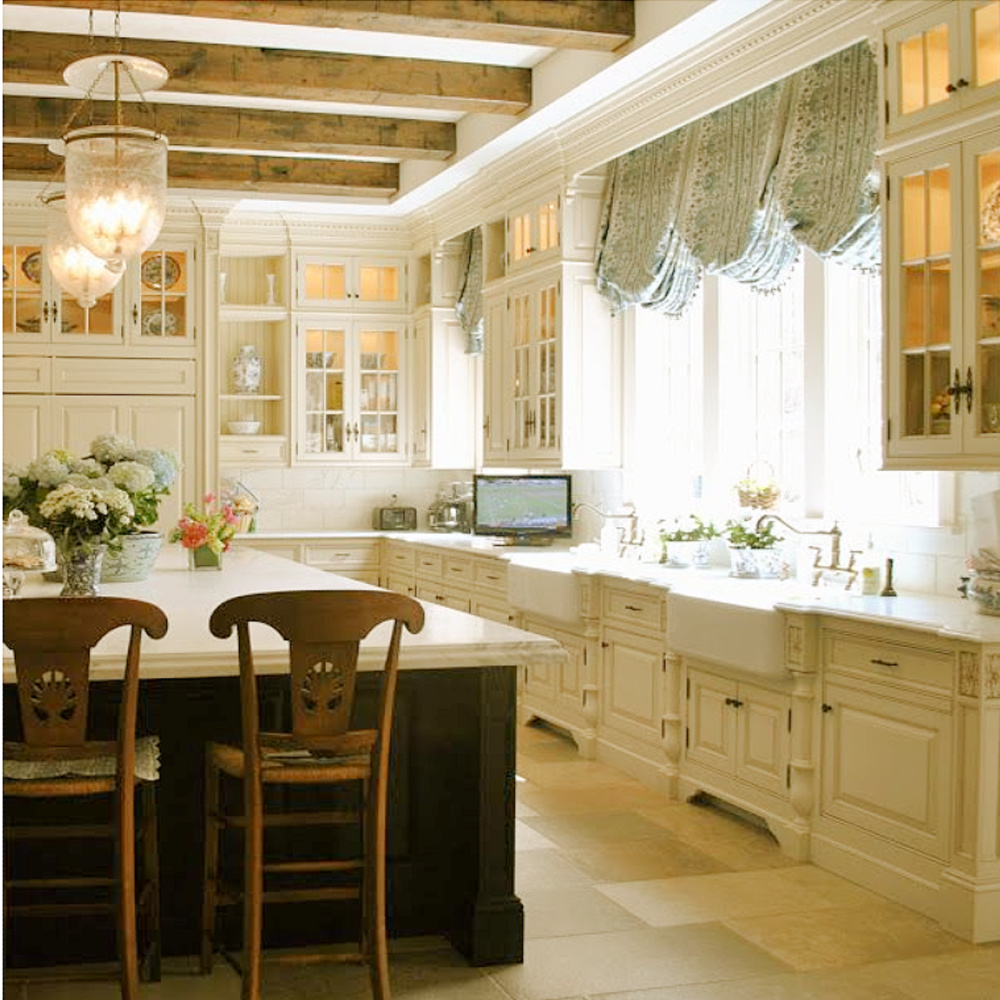 Gorgeouso blue and white French country kitchen with island, beams, and stone flooring - The Enchanted Home.