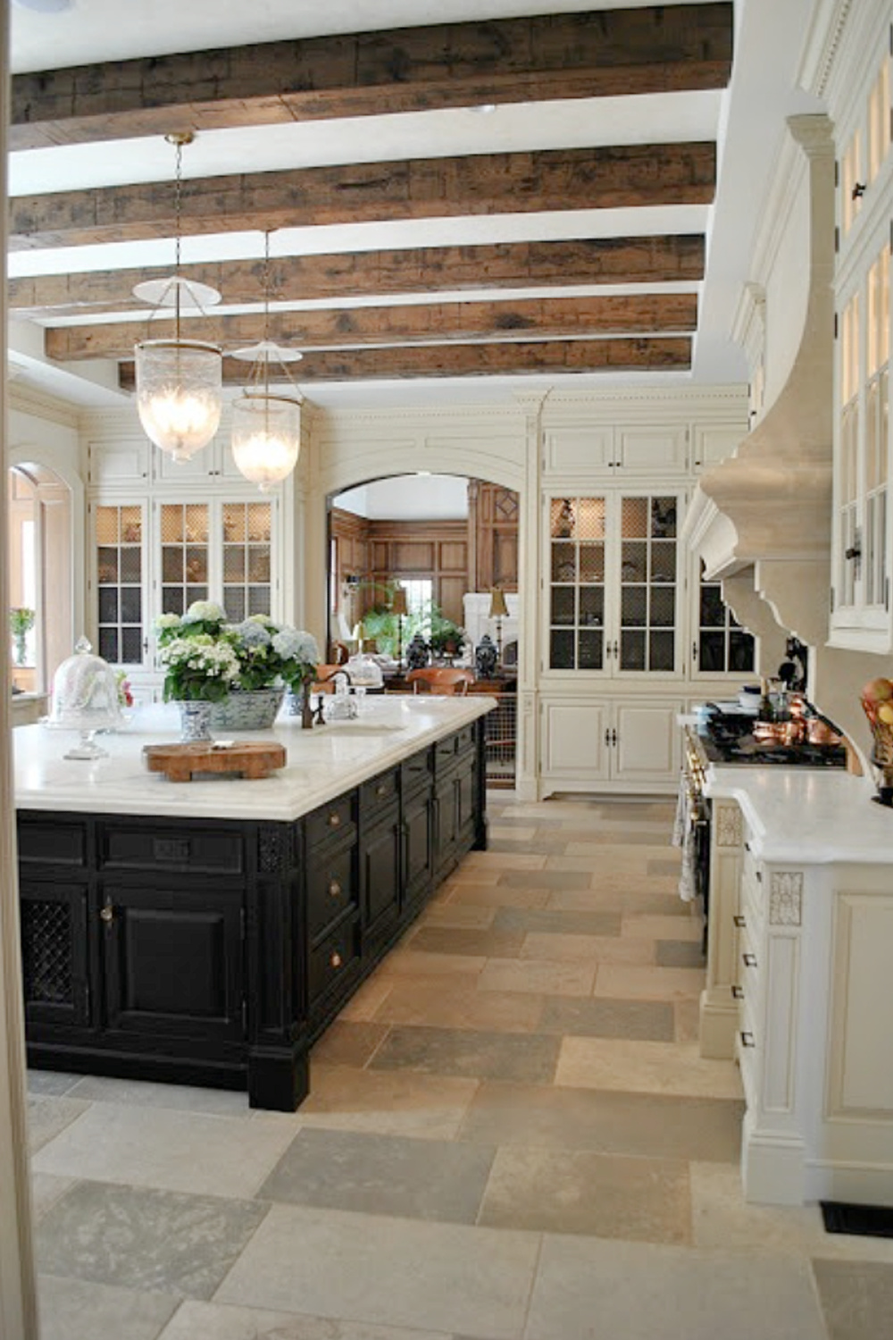 Stunning French Country kitchen with black island, wood celing beams, bell jar pendant lights, and marble counters. #FrenchCountry #kitchendesign