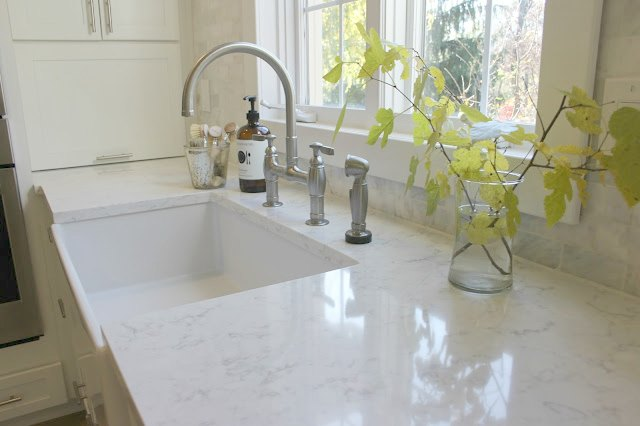 Viatera Minuet quartz countertops and farm sink in white serene Shaker style kitchen by Hello Lovely Studio