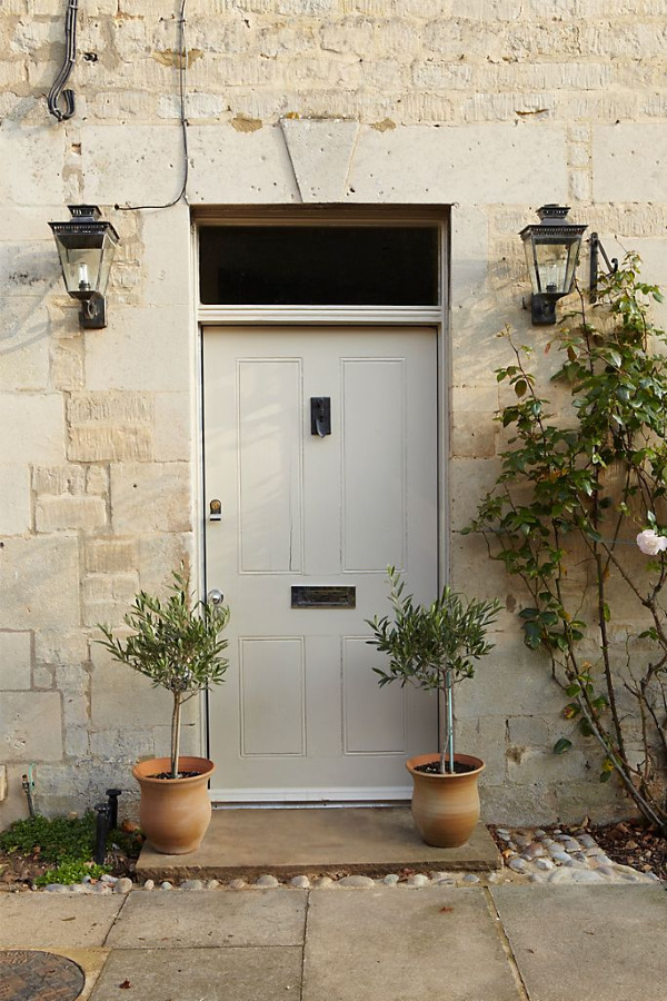 Stony Ground Farrow & Ball paint color is on this gorgeous front door of an English stone cottage with topiaries on porch. #paintcolors #stonyground #farrowandball #interiordesign #exteriorpaintcolors #frontdoorpaintcolor