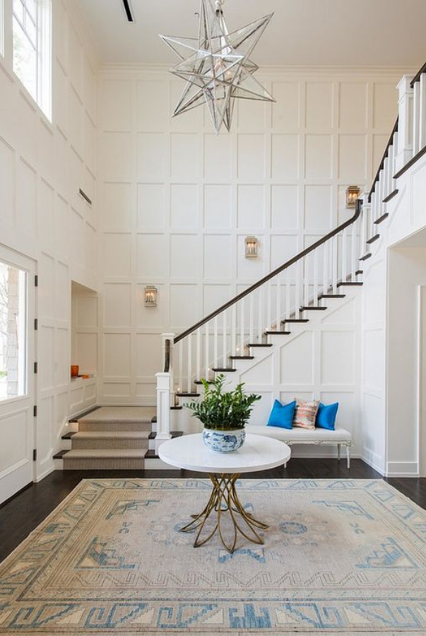 Wimborne White paint color by Farrow & Ball in a magnificent home's entry with soaring ceilings, paneled walls, and elegant staircase. #wimbornewhite #farrowandball #paintcolors #bestwhitepaintcolors
