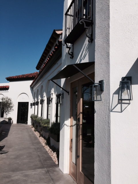 Exterior Magnolia Table Restaurant in Waco with black and white design, arches, window boxes, and modern farmhouse sconce lighting. #magnoliatable #exterior #restaurant #fixerupper