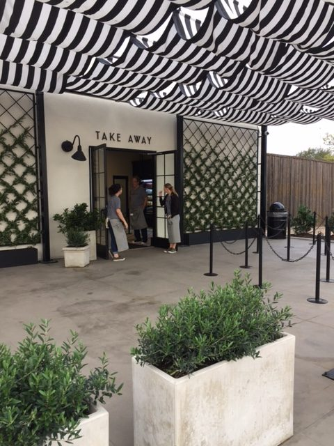 Magnolia Table Take out area with black and white stripe awning, living wall trellises, and concrete planters. #magnoliatable #blackandwhite #restaruant #fixerupper #takeout