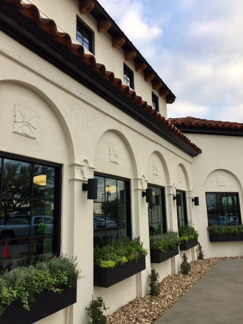 Magnolia Table restaurant exterior with black window boxes full of greenery. #magnoliatable #fixerupper #restaurant #waco