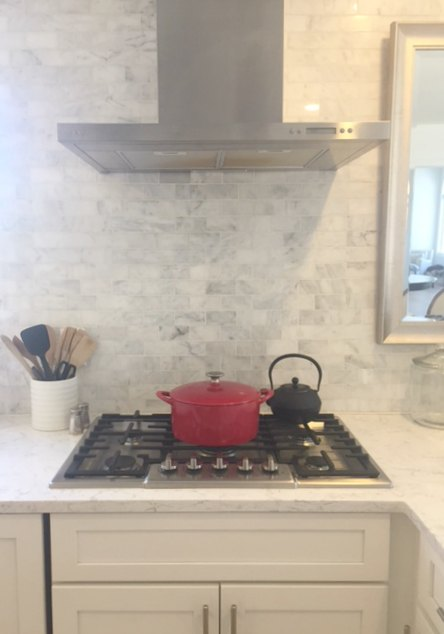 Red cast iron dutch oven on cooktop with marble subway tile backsplash. #red #dutchoven #marblebacksplash