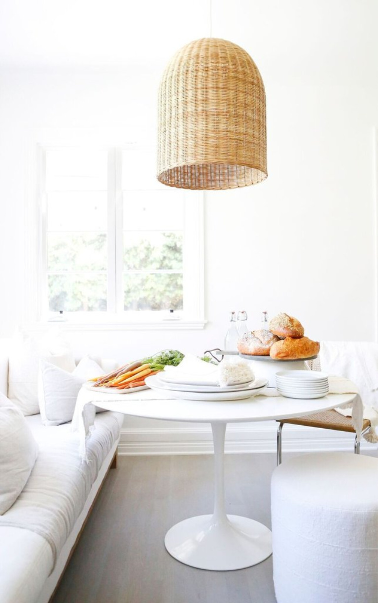All white modern rustic decor in a chic breakfast nook in the kitchen with Saarinen table, sofa, and wicker pendant light. Erin Fetherston's white California farmhouse is chic yet livable with a Midcentury Modern twist. #allwhite #saarinen #whitekitchen #midcentury #breakfastnook