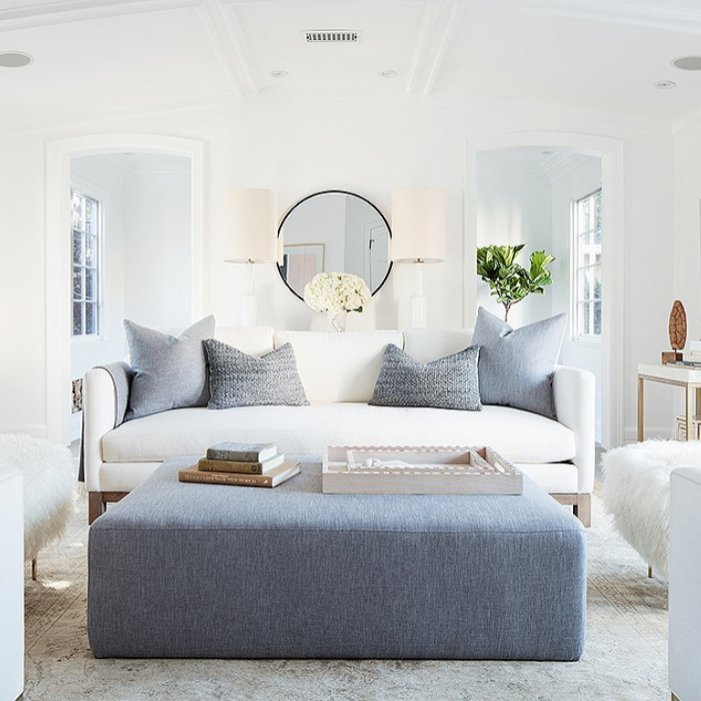 "Midcentury modern style in a modern farmhouse living room with white decor. ""I wanted every wall to make sense, to have its own vignette,"" says Alex. It's also a flexible design scheme—the ottoman adds extra seating and can be ""scooched up for cozier conversations during parties."" #blueandwhite #livingroom #modernrustic #serenedecor #interiordesign"