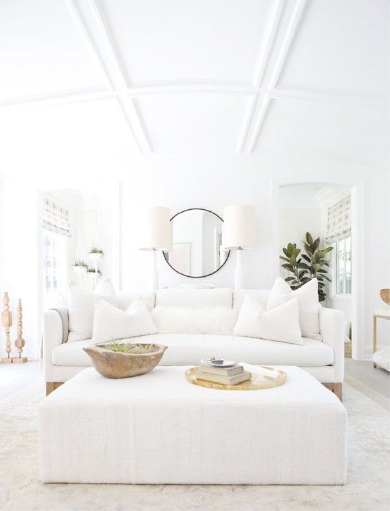 All white living room with white linen sofa, upholstered ottoman, rustic dough bowl, brass accents, and California modern farmhouse chic by Erin Fetherston. #whitedecor #livingroom #whiteonwhite #toneontone #interiordesign #whitelinen #modernrustic