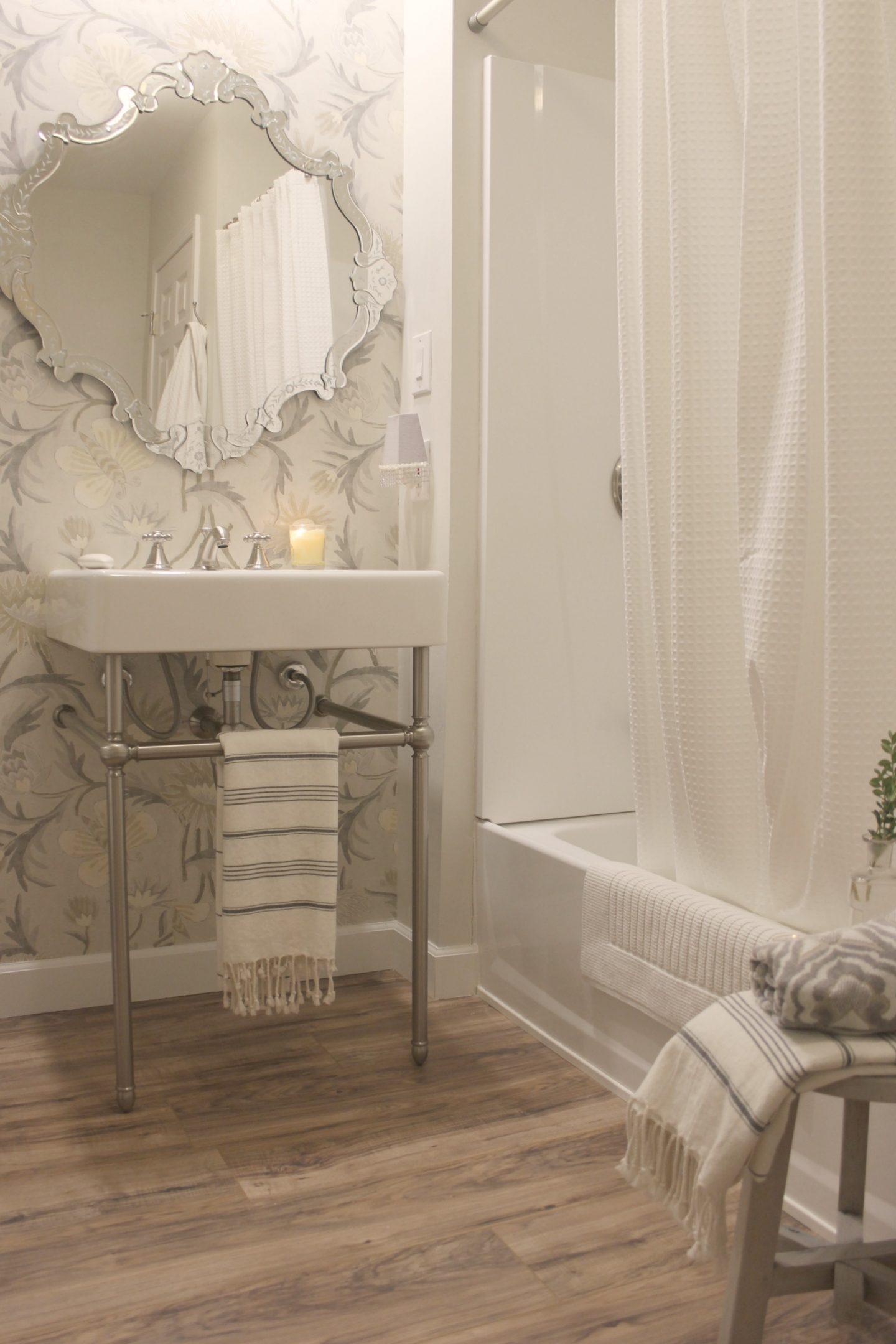 Classic bathroom design with console sink, Venetian mirror, Turkish towel, and wood look floor.