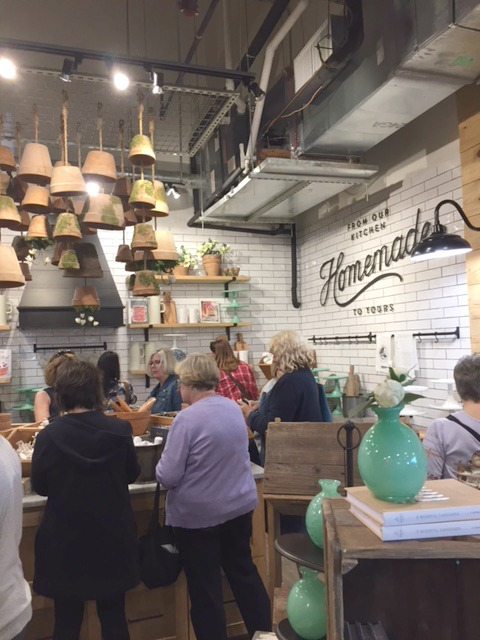 The interior of Magnolia Market at the Silos with white subway tile, terracotta pots suspended from the ceiling, and farmhouse style decor. #magnoliamarket #silos #waco #fixerupper