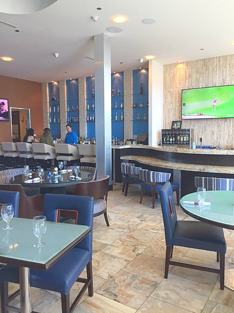 Brazos Bar & Bistro with Travertine floor, blue decor, and Midcentury Modern details within #hotelindigo in #Waco