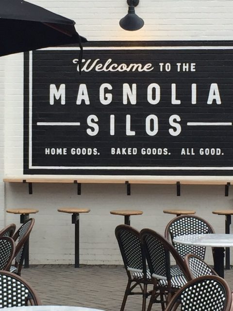 Magnolia Market Silos white brick wall of Silos Baking Co. with bar stools, Parisian bistro chairs, and black and white decor. #magnolia #silos #bakery #fixerupper