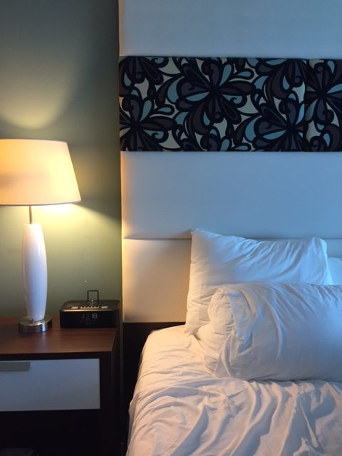 Hotel Indigo upholstered headboard and night table with Midcentury Modern white lamp. #hotelindigo #bedroomdecor #midcenturymodern
