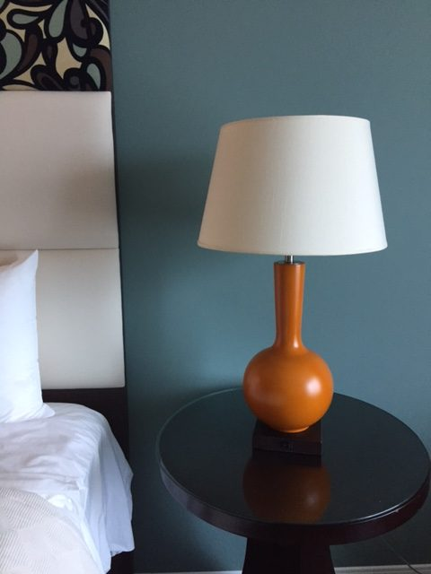 Teal blue wall and orange Midcentury modern lamp at Hotel Indigo Waco. #bedroomdecor #orange #teal #Midcenturymodern