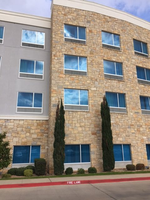 Facade of Hotel Indigo Waco-Baylor with Stone & Blue Windows #hotelindigo