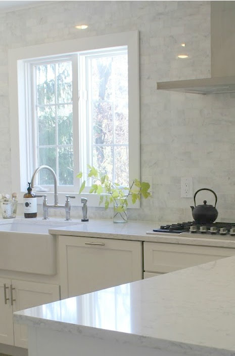 Timeless, tranquil, French farmhouse and European country style white kitchen has soft linen, polished marble backsplash and Viatera Minuet white quartz countertop. Hello Lovely Studio.