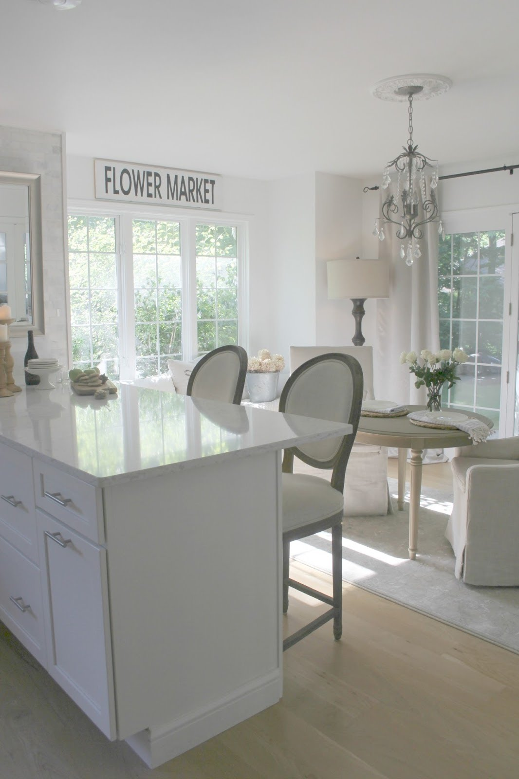Serene French Country kitchen decor with white quartz counter, linen upholstered bar stools, Flower Market sign, and crystal chandelier. Design by Hello Lovely Studio. #kitchendecor #kitchendesign #whitekitchen #frenchcountry #serene #elegantdecor #hellolovelystudio