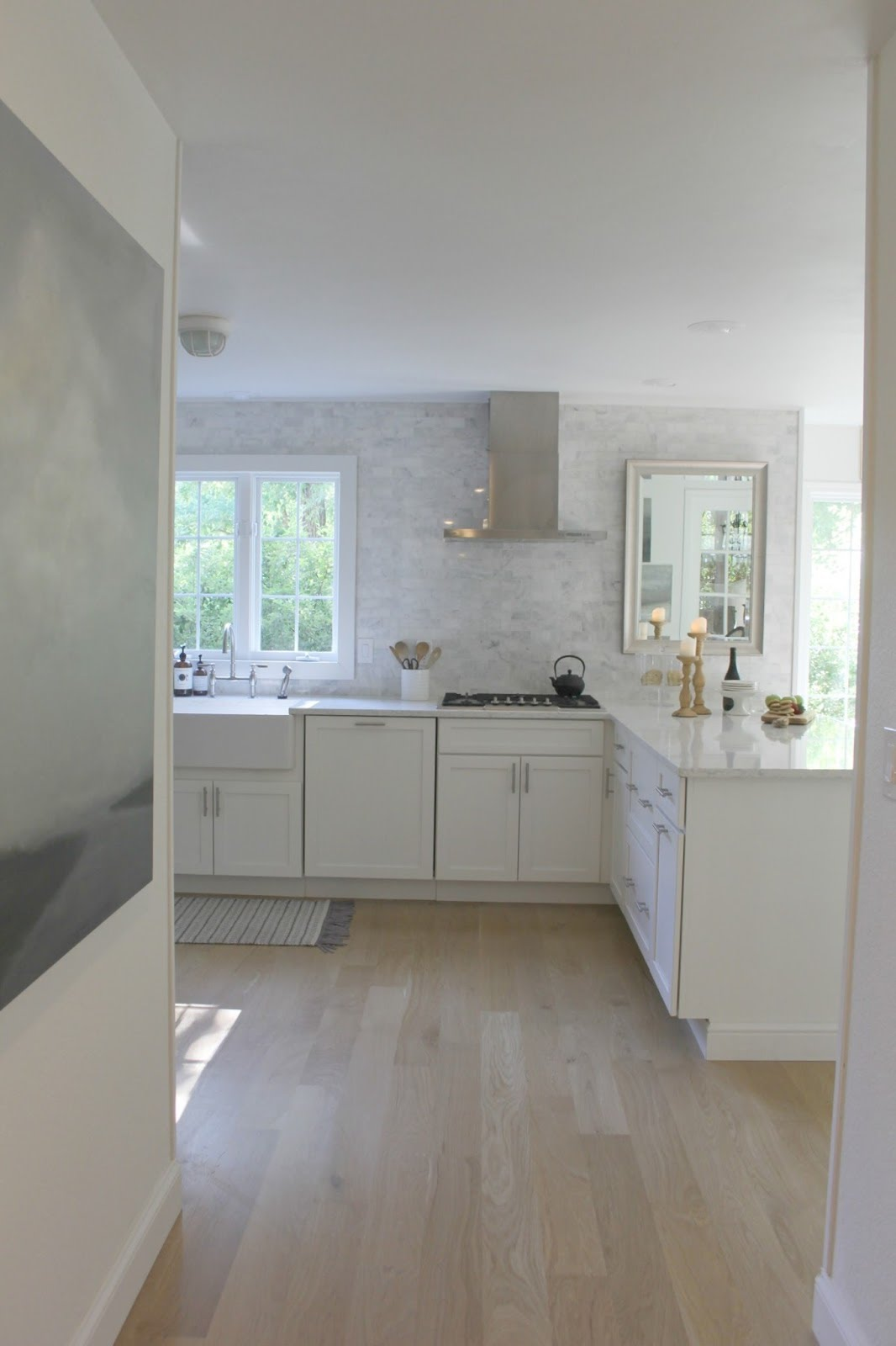Serene white modern farmhouse kitchen with European inspired details. Shaker cabinets, marble subway tile, white oak hardwood, and abstract painting on wall. #whitekitchen #kitchendecor #modernfarmhouse #kitchenideas #serene #hellolovelystudio #whitedecor