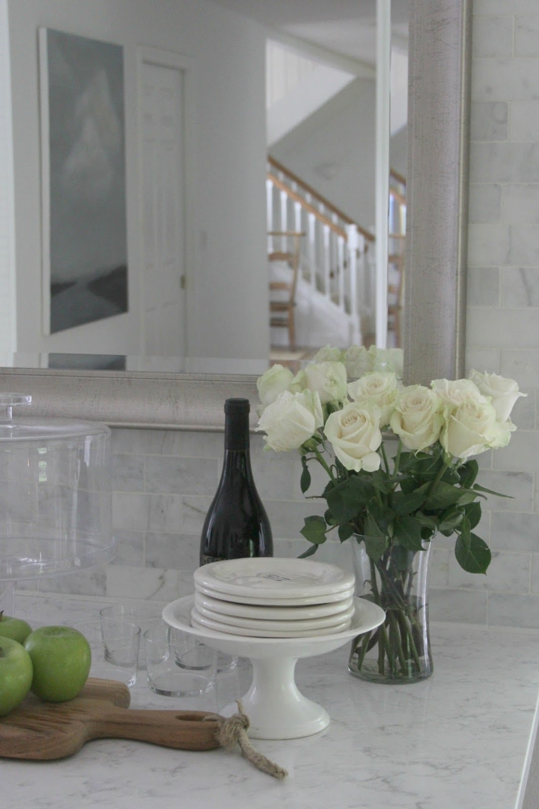 Serene white kitchen decor with Viatera Minuet countertop, marble subway tiles, white roses, and silver framed mirror. #whitekitchen #whitedecor #kitchendecor #subwaytile #quartz #whiteroses #hellolovelystudio #timelessdesign #serene