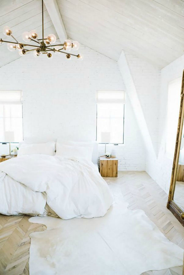 Stunning and serene all white decor in a bedroom design by Leanne Ford. Midcentury-modern style, Sputnik chandelier, herringbone flooring, and hide rug. #whitebedroom #allwhite #bedroomdecor #midcenturymodern #leanneford