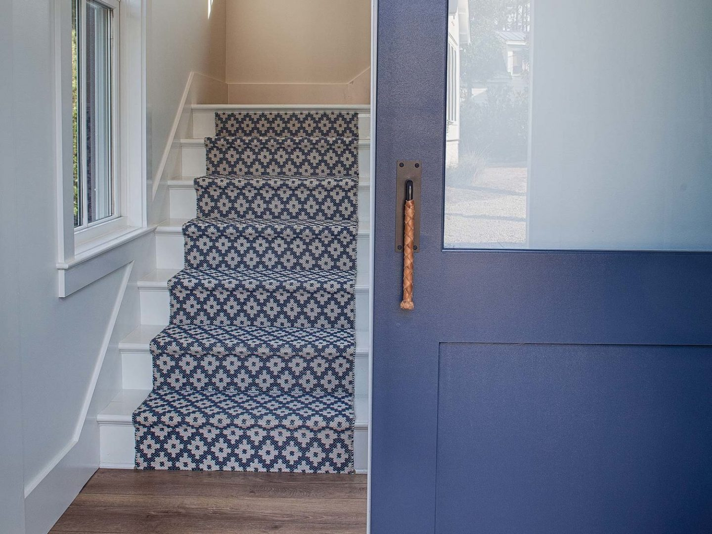 Blue stair runner and door. Board and batten coastal cottage in Palmetto Bluff with modern farmhouse interior design by Lisa Furey.
