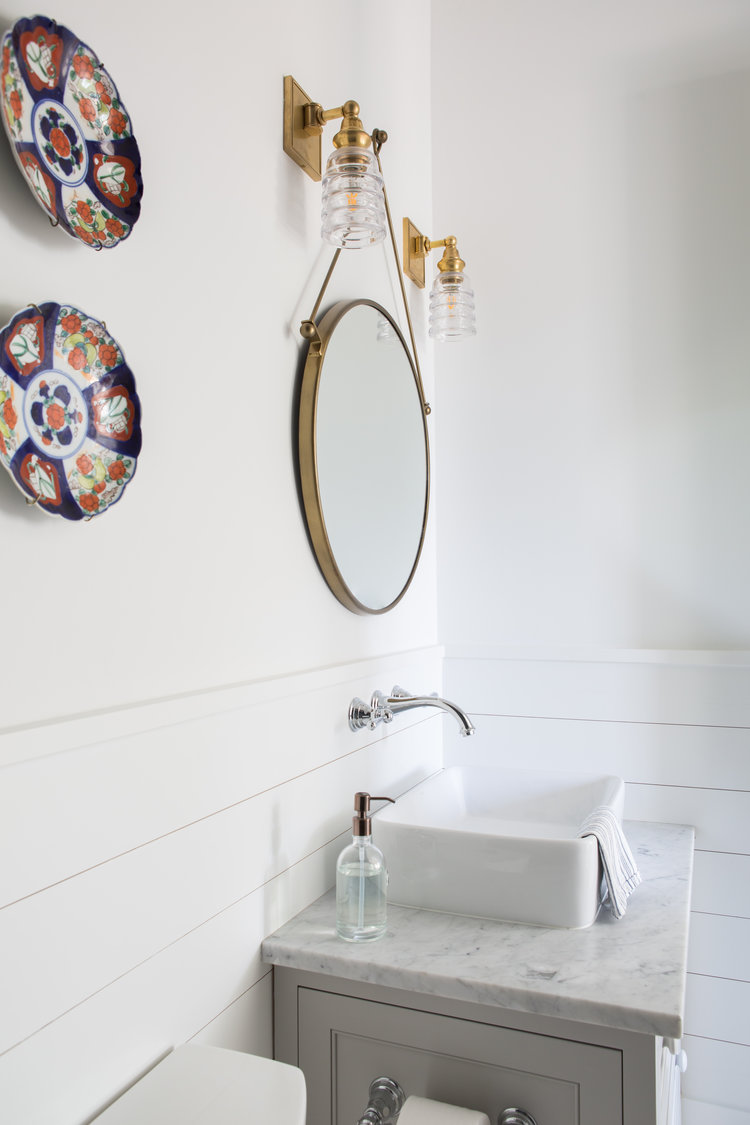 Coastal bathroom with shiplap, vessel sink, and round mirror.Board and batten coastal cottage in Palmetto Bluff with modern farmhouse interior design by Lisa Furey.
