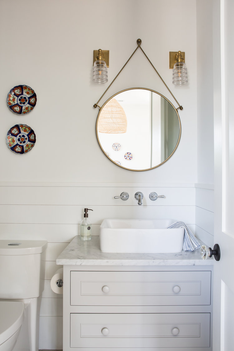 Coastal bathroom with vessel sink, shiplap, and round mirror. Board and batten coastal cottage in Palmetto Bluff with modern farmhouse interior design by Lisa Furey.