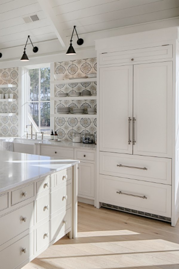 Lisa Furey's white coastal cottage kitchen in Palmetto Bluff inspires with its colorful tile, quiet grey island, and modern black wall sconces.