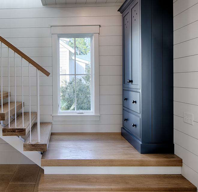 White oak hardwood floor and stairs in entry with shiplap on walls and tall cabinet painted blue. Board and batten coastal cottage in Palmetto Bluff with modern farmhouse interior design by Lisa Furey.