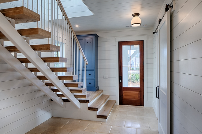 White oak staircase, blue painted cabinet, and shiplap in entryway. Board and batten coastal cottage in Palmetto Bluff with modern farmhouse interior design by Lisa Furey.