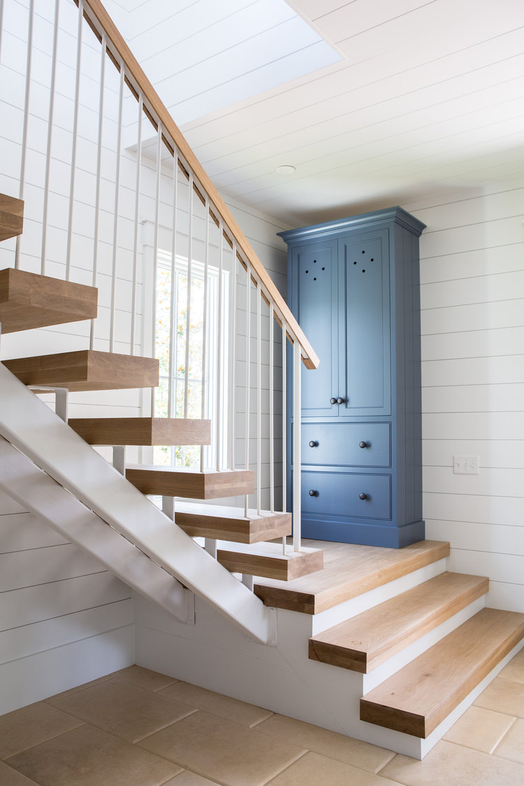 White oak staircase, shiplap, and blue armoire in entry. Board and batten coastal cottage in Palmetto Bluff with modern farmhouse interior design by Lisa Furey.