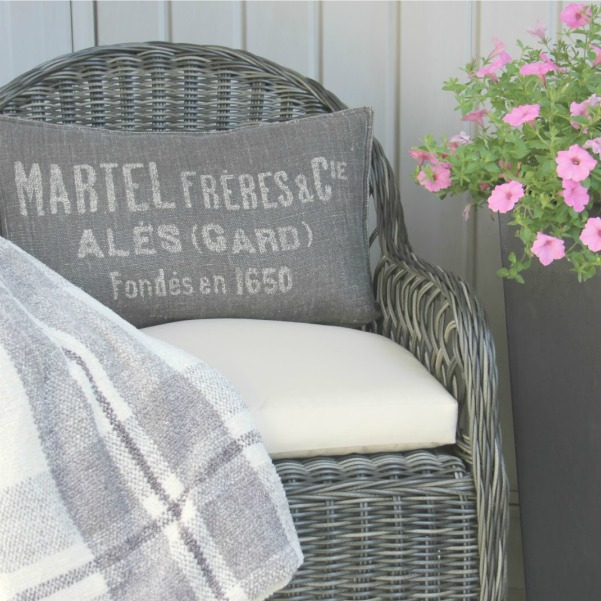 Grey rattan outdoor chair with ivory cushion and French lettering on a grey pillow on the front porch. Design by Hello Lovely Studio. #outdoorliving #rattanchair #grey #Frenchcountry