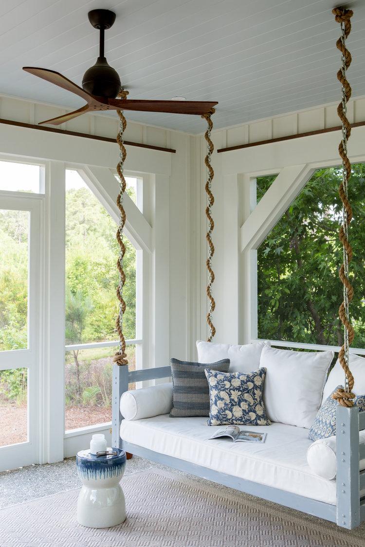 Blue painted porch ceiling and porch swing. Board and batten coastal cottage in Palmetto Bluff with modern farmhouse interior design by Lisa Furey. Come peek at Charming Porch Inspiration & Decor Ideas.