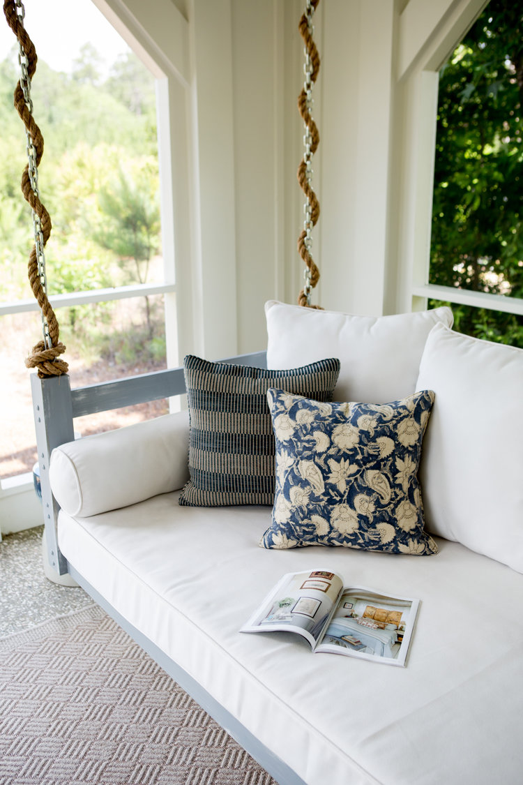 Porch swing. Board and batten coastal cottage in Palmetto Bluff with modern farmhouse interior design by Lisa Furey.