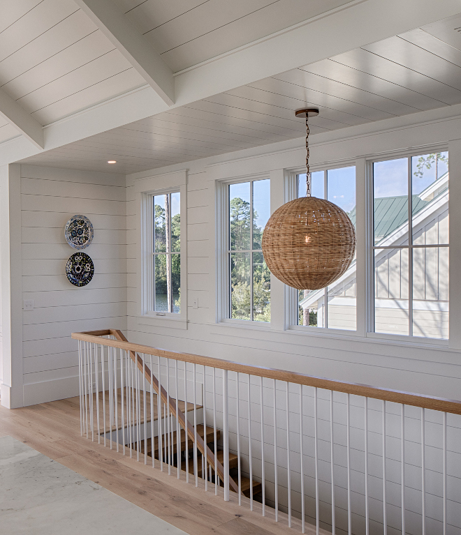Staircase with rattan globe chandelier. Board and batten coastal cottage in Palmetto Bluff with modern farmhouse interior design by Lisa Furey.