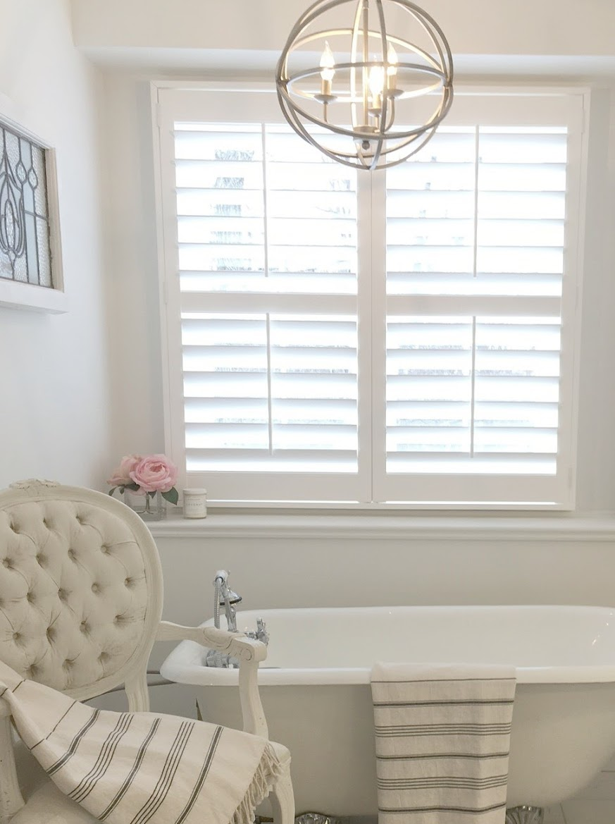 "White classic bathroom with plantation shutters, vintage clawfoot tub, and Louis style tufted accent chair. Stripe Turkish towels and sphere pendant in an antiqued silver finish. Wall color is Benjamin Moore ""White.."" Hello Lovely Studio. #bathroomdesign #hellolovelystudio #plantationshutters #louischair #clawfoottub #benjaminmoorewhite"