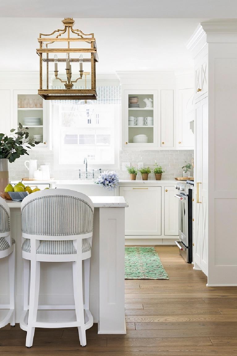 Soft white kitchen with white terracotta subway tile backsplash white quartz countertop and white farmhouse sink. Come see 36 Best Beautiful Blue and White Kitchens to Love! #blueandwhite #bluekitchen #kitchendesign #kitchendecor #decorinspiration #beautifulkitchen