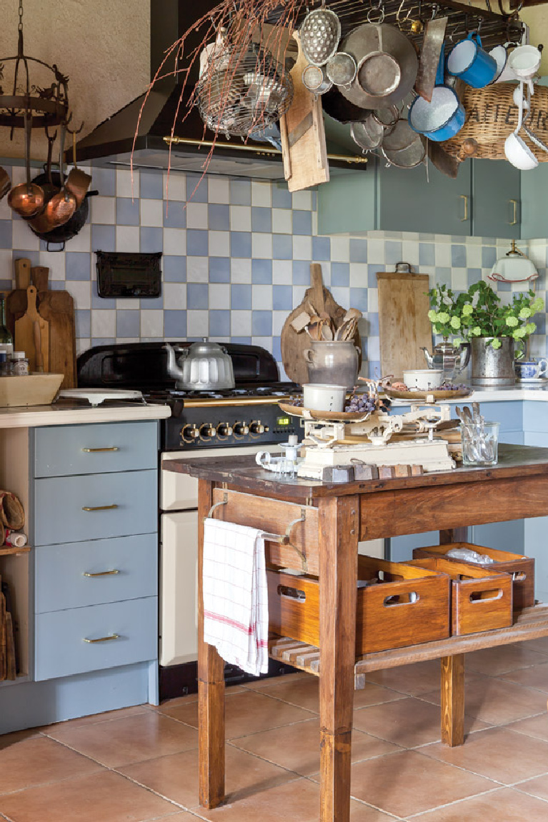"""The kitchen features blue and white tiles found in a French market and a wooden table once used for drying cheeses. """"Our interior decoration is not something we managed in a short period,"""" says Clementine, """"but is the result of a lifetime of collecting nice brocante furniture and vintage items."""" Come see 36 Best Beautiful Blue and White Kitchens to Love! #blueandwhite #bluekitchen #kitchendesign #kitchendecor #decorinspiration #beautifulkitchen"""