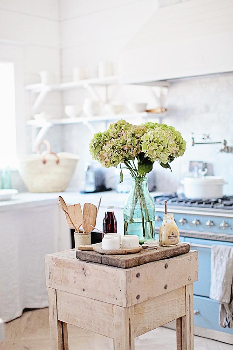 French farmhouse kitchen with blue Lacanche range, butcher block work table, hydrangea, and glorious white - Dreamywhites. #frenchfarmhouse #kitchens #frenchcountry #lacanche #interiordesign