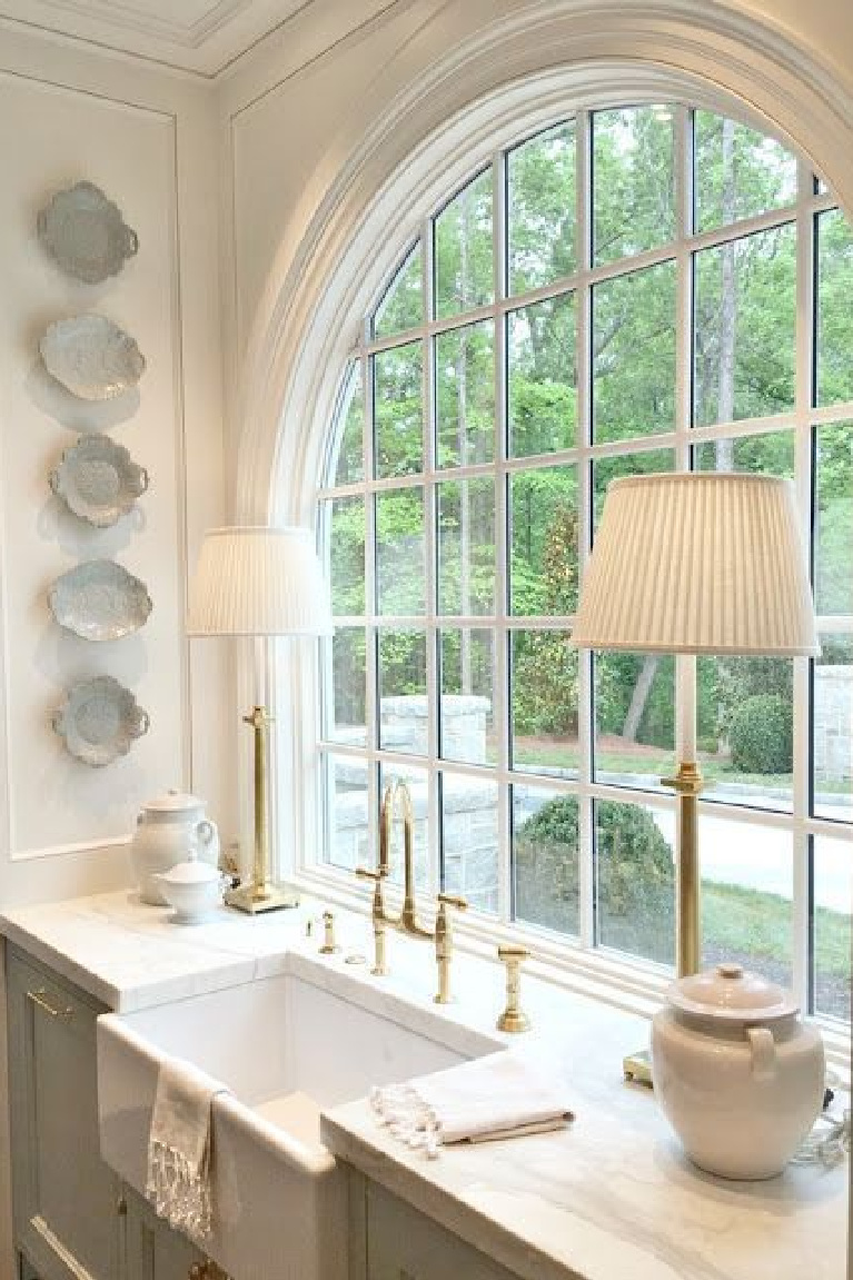 French Country interior design inspiration from a classic kitchen with blue and white decor! Stunning traditional style kitchen with light blue painted cabinets, hammered brass hardware arch window over farm sink, and waterfall marble island.