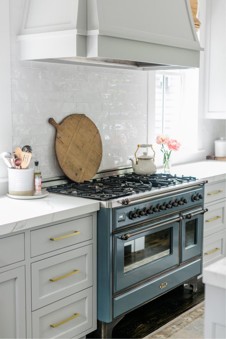 Beautiful modern farmhouse kitchen with light grey cabinets, brass hardware, and blue Ilve Majestic range - Finding Lovely. #modernfarmhouse #kitchendesigns #ilvemajestic #greykitchens