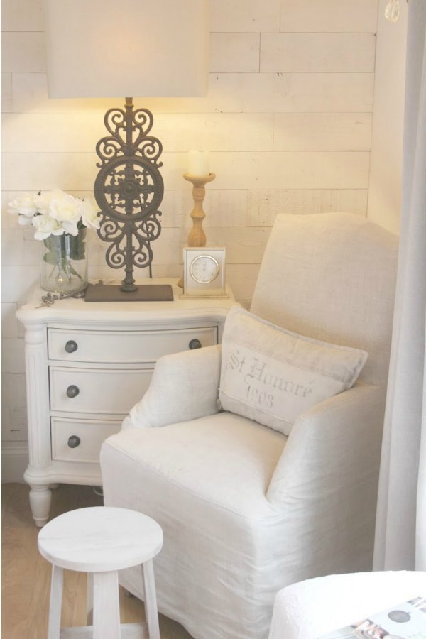 10 Tips to Decorate Without Spending a Dime! A Belgian linen slipcovered arm chair in my bedroom from RH. Cottage style nightstand with Paris gate lamp (RH) and Stikwood (Hamptons) reclaimed wood planks on wall for a rustic chic look. #bedroomdecor #neutral #stikwood #hamptons #belgianlinen #hellolovelystudio