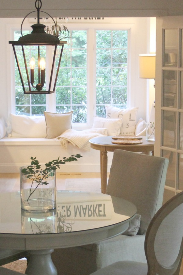Hello Lovely Studio's serene white kitchen with window seat and dining room with lantern. #hellolovelystudio #interiordesign #kitchen #windowseat #serenedecor #whitedecor #benajminmoorewhite