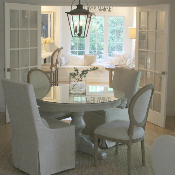 French country dining room with round pedestal table and rustic lantern. Hello Lovely Studio.